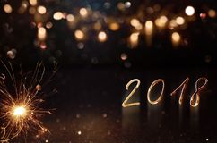 New year background 2018 with sparkler. New year greetings 2018 with festive golden bokeh and sparkler Royalty Free Stock Photography