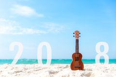 New Year 2018 with Guitar ukulele for relax on the beautiful beach and blue sky background for season and holiday. Stock Image