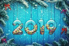 New year 2019. Happy new year 2019 background! Set of transparent glass with multicolored candy and sweets hang on a snowy Christmas tree branch royalty free stock photography