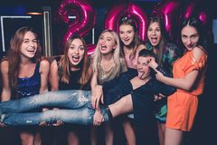 New Year happy celebration. Funny friends. Selfie. One male in girls company in night club, fun background, happiness, pickup concept royalty free stock image