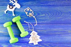 New Year Healthy Goals and Resolutions concept. Dumbbells and decorations on blue wooden background
