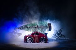 Miniature car with fir tree on Snowy Winter Fores, or toy car carrying a christmas tree and at night time Stock Image