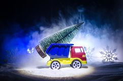 Miniature car with fir tree on Snowy Winter Fores, or toy car carrying a christmas tree and at night time Royalty Free Stock Photography