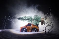 Miniature car with fir tree on Snowy Winter Fores, or toy car carrying a christmas tree and at night time. New year holiday concept. Miniature car with fir tree Royalty Free Stock Image