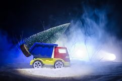 Miniature car with fir tree on Snowy Winter Fores, or toy car carrying a christmas tree and at night time. New year holiday concept. Miniature car with fir tree Stock Images