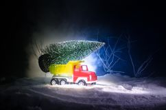 Miniature car with fir tree on Snowy Winter Fores, or toy car carrying a christmas tree and at night time. New year holiday concept. Miniature car with fir tree Royalty Free Stock Photography