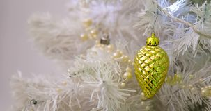 New Year Holiday - cones on the Christmas tree. Background with golden balls and cones on the Christmas tree. White fir tree with flashing lights garlands stock video footage