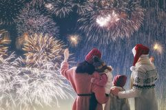 Family watching fireworks. New Year holiday. Parents and daughters children girls are watching fireworks. Happy family on snowy winter walk in nature. Holidays royalty free stock photo