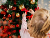 Close up of little girl decorating christmas tree Stock Image