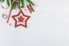 New year holidays wooden background decorated with green fir tree branch, red star, candy cane and wooden toy sledge. Flat lay stock images