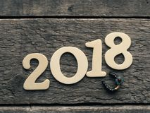 New Year 2018 with a horse shoe on wood. New Year 2018 with a horse shoe on a rustic wooden plank, Happy New Year and Good luck Stock Image