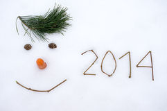 New Year 2014. The image of 2014 and the face made of cones, branches and carrots on snow Stock Photography