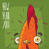 New Year 2017 inscription and cock or rooster. Cartoon from close-up of portrait funny and surprised cock or rooster on green background. New Year 2017 Stock Images