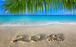 New Year 2018 Inscription written and Caribbean sea with green palm . New Year 2018 Inscription written in the wet Caribbean sand Royalty Free Stock Photography