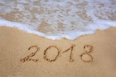New Year 2018 Inscription written and Caribbean sea . New Year 2018 Inscription written in the wet Caribbean sand Royalty Free Stock Images