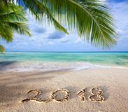 New Year 2018 Inscription written and Caribbean sea with green palm . Royalty Free Stock Photos