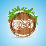 New year lettering on round wood border with snowy fir tree branch and cones on blue. Background Royalty Free Stock Photo