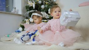 New year, little sisters in pink dresses sit on plaid with gift boxes against the background of christmas tree with stock video