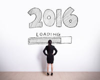 New Year is loading now. Back view of business woman look 2016 text on white wall background Royalty Free Stock Images