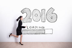 New Year is loading now. Successful business woman running and hold laptop computer with 2016 text and white wall background Royalty Free Stock Photos