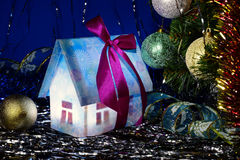New Year luminous house and Christmas ball. Christmas present under a Christmas tree Royalty Free Stock Photography