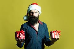 New year man with presents. One handsome senior new year man with long black beard in shirt and red santa claus hat holding two wrapped present boxes in hands Royalty Free Stock Photography