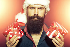 New year man with presents. Portrait of one senior new year man with long black beard in shirt and red santa claus hat holding two wrapped present boxes in hands Royalty Free Stock Photos