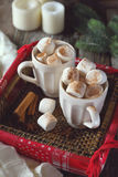 New Year marshmallows in two cups and candles Royalty Free Stock Photo