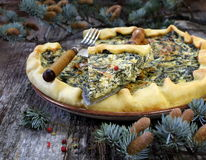 New Year mood: spinach quiche and pine branches Stock Photos