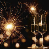 New year motif with fireworks and champagne. New Year motif at night with fireworks bokeh and two champagne glasses Royalty Free Stock Photos