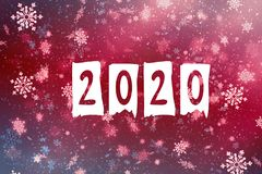 New year-2020. New year`s composition, the concept of the New year. Inscription 2020 red background with painted snow and snowflak stock image