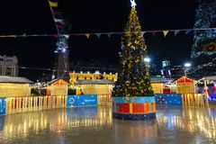 Free New Year Night Scene. Festive Christmas Tree With Decorations On The Rink On The Background Of Christmas Illumination And Night Sk Stock Photo - 135866900