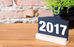 New year 2017 number on blackboard sign and green plant on wood. Table at brick wall Stock Image