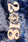 New Year number 2018 from wood. Wooden digit 2018, symbol of New Year on blue and silver tinsel sparkling background. The best wishes in New Year 2018 stock photos