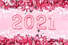 2021 New Year numbers metallic foil balloons. Pink tinsel decor background