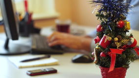 New Year office decoration. A small Christmas tree standing on the working desk in the office with a man typing on the computer stock video footage