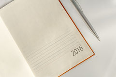 New Year 2016 office organizer calendar and sliver ballpen. Selective focus Royalty Free Stock Photos
