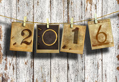New year 2016. In old photo hanging on clothesline on wood background Stock Photo