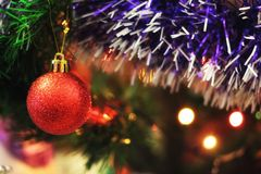 New Year Orange Ball On Tree. Christmas orange ball on the Christmas tree, tinsel, lights create a beautiful new year and Christmas mood Stock Image