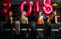 New Year party at bar. Beauty females. Stylish women group, friends celebration. Club background, festive mood Stock Photos