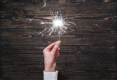 New year party burning sparkler closeup in female hand on black background. Woman holds glowing holiday sparkling hand fireworks, shining fire flame. Christmas Royalty Free Stock Photography