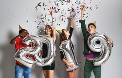 New Year party. company of cheerful friends with ballonss numbers 2019 royalty free stock photos