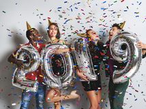 New Year party. company of cheerful friends with ballonss numbers 2019 royalty free stock images