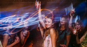 New Year party at night club in blurred motion. Joyful friends with cocktails at Christmas discotheque, active happy company with drinks, modern youth life Royalty Free Stock Image