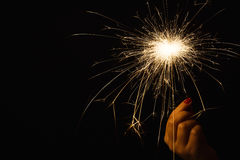 New year party sparkler in female hand on black background. New year party burning sparkler closeup in female hand on black background. Woman holds glowing Stock Image