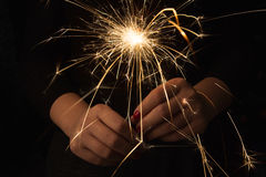 New year party sparkler in female hands on black background. New year party burning sparkler closeup in female hands on black background. Woman holds glowing Stock Photography