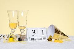 New Year party still life. With two empty glasses of Champagne and a date block showing 31st December with streamers. Copy space on the background for your own Stock Photos