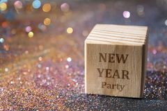 New year party text on cube. Wood Cube with New year party text on glitter Stock Photography