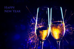 New Year party time with two champagne glasses and sparklers aga. Party time with two champagne glasses and fireworks of sparklers against a dark blue background Stock Image