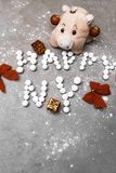 New year pig, 2019, toy pig on grey background Christmas decor, postcard. Red gifts toys, bows, balls royalty free stock photo